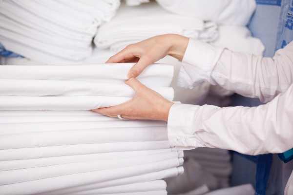Closeup of white bedsheets stacked in store room